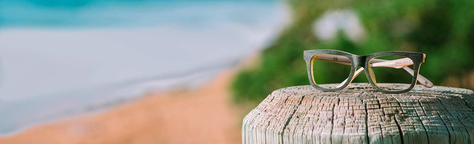 briller fra extra optical på en strand med sol og blå himmel
