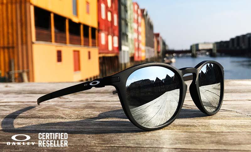 Oakley solbriller på en benk med fine bygg i bakgrunn