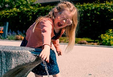 jente med solbriller som leker med vann