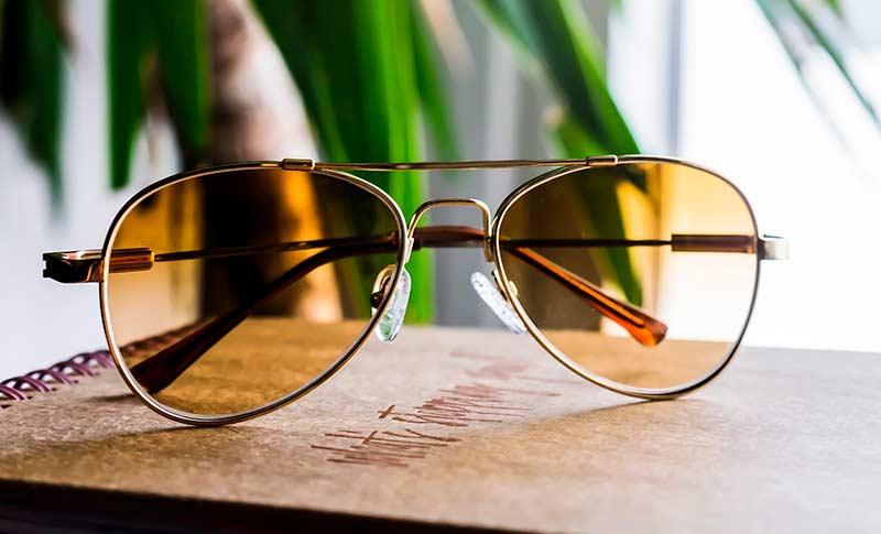 pilotsolbriller med gule glass som ligger på et bord foran en plante